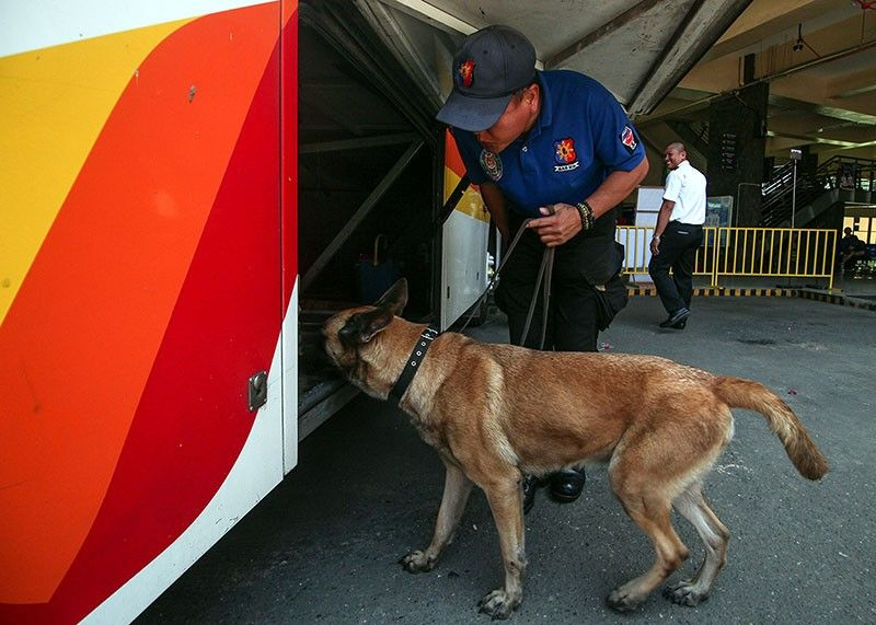 BAGUIO. A security personnel and his K-9 dog inspect a bus station in Baguio City to ensure the safety and security of passengers. As the summer season begins, transport groups prepare for the influx of tourists in Baguio and nearby provinces. (Photo by Jean Nicole Cortes)