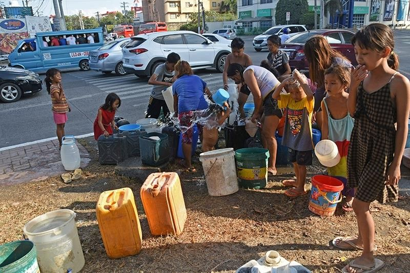 PRECIOUS RESOURCE. Residents of Barangay Mabolo, Cebu City take advantage of a busted Metropolitan Cebu Water District (MCWD) pipe A maintenance team was quickly dispatched to repair it. (SunStar photo / Allan Cuizon)
