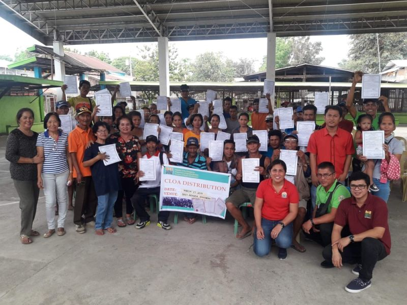 BACOLOD. The 41 farmers from Hinigaran, who received land titles, with the Department of Agrarian Reform-Negros Occidental II personnel during the distribution of certificates of land ownership award in Barangay Aranda. (Contributed photo)