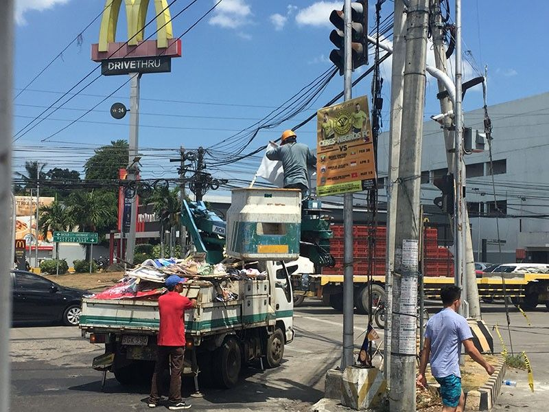 BACOLOD. The Commission on Elections removes illegal campaign posters along Lopue's East in Bacolod City. (Merlinda A. Pedrosa)