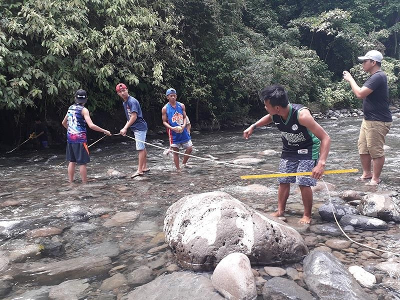 Volunteers from Bantayo Aweg, a local community-based organization that monitors the condition and quality of Panigan-Tamugan River, test the stream flow discharge parameter of the river. (Photo by Jessa Mae B. Reston, USeP intern.)
