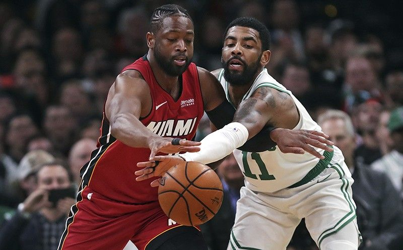Boston Celtics guard Kyrie Irving (11) reaches in on a steal-attempt against Miami Heat guard Dwyane Wade (3) during the first quarter of an NBA basketball game in Boston, Monday, April 1, 2019. (AP Photo)