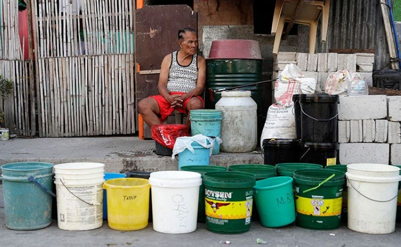 MANILA. A man sits beside rows of pails as he waits for water trucks return to their area after several days without water in Mandaluyong City on Thursday, March 14, 2019. (AP)