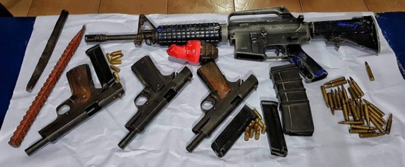 BACOLOD. Police seize several firearms, ammunition and an explosive from two notorious members of Epogon robbery group in Barangay Sum-ag, Bacolod City. (Contributed photo)