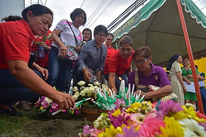 DAVAO. City officials and relatives of the victims of the Sasa Wharf Bombing offer candles and prayers at the blast site on April 2, 2019, during a program commemorating the 16th year anniversary of the incident that killed 16. (Photo by Macky Lim)