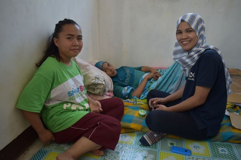 MARAWI. c (center) though bed ridden, still agreed to have her photo taken with Hidaya Manioba (left) of the Community and Family Services International and her daughter (right). (Riz P. Sunio)