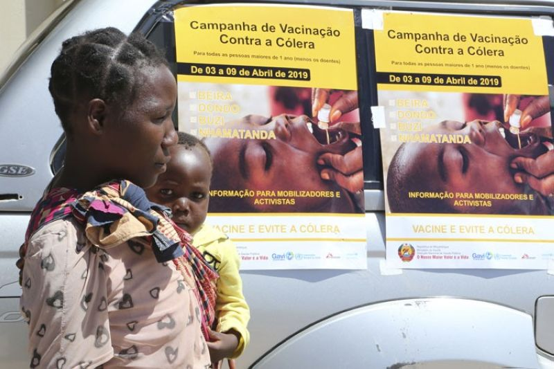 MOZAMBIQUE. A woman and her baby walk past cholera vaccination campaign posters on the first day of the cholera vaccination programme at a camp for displaced survivors of cyclone Idai in Beira,Mozambique, Wednesday, April, 3, 2019.  A cholera vaccination campaign is kicking off to reach nearly 900,000 cyclone survivors in Mozambique as officials rush to contain an outbreak of the disease. (AP)
