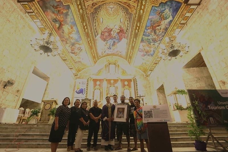 DIBUHO KISAME QR-CODED. The Sts. Peter and Paul Parish in Bantayan, Cebu has been coded for quick response (QR) by InnoPub Media in partnership with Smart Communications. Parish priest Fr. Joselito Danao (center) received on April 4, 2019 the QR markers for the 438-year-old Catholic church, its museum that displays the papal indult allowing Bantayanons to eat meat during Lent, and the ceiling mural dubbed Dibuho Kisame. In the picture with Fr. Danao are (from left) Raquel Tinga and Frankie Despi of the parish pastoral council, Smart AVP for public affairs Atty. Jane Paredes, donor Michael Enriquez, and DK artists Alvin Pastor, Cheno Encarnacion and Aldwin Canoy. (Alex Badayos)