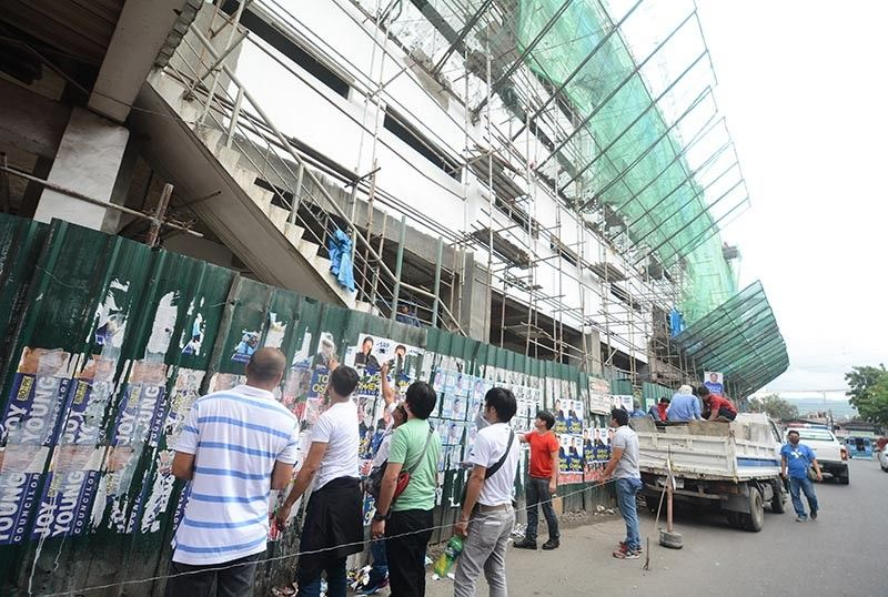 FACE OF THE DEFIANT. Commission on Elections personnel remove posters of candidates outside the Cebu City Medical Center construction site on Panganiban St., Cebu City on April 8, 2019. They removed campaign materials outside the common poster areas allowed by the commission. (SunStar photo / Amper Campaña)