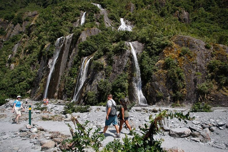 NEW ZEALAND. In this February 7, 2016 file photo, tourists walk past waterfalls at the Franz Josef Glacier in New Zealand. The Fox and Franz Josef glaciers have been melting at such a rapid rate that it has become too dangerous for tourists to hike onto them from the valley floor, ending a tradition that dates back a century. (AP)