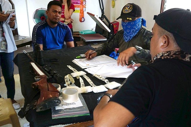 KONSEHAL DAKPAN: Mga operatiba sa Provincial Drug Enforcement Unit sa Cebu Provincial Police Office ang mipahigayon og makuting pakisusi sa nasakmit nga air gun ug upat ka dagkong pakite nga gituohang shabu atol sa gipahigayong ronda sa balay ni Barangay councilor Bimbo Ramos sa Lawaan III, dakbayan sa Talisay. (Alex Badayos)