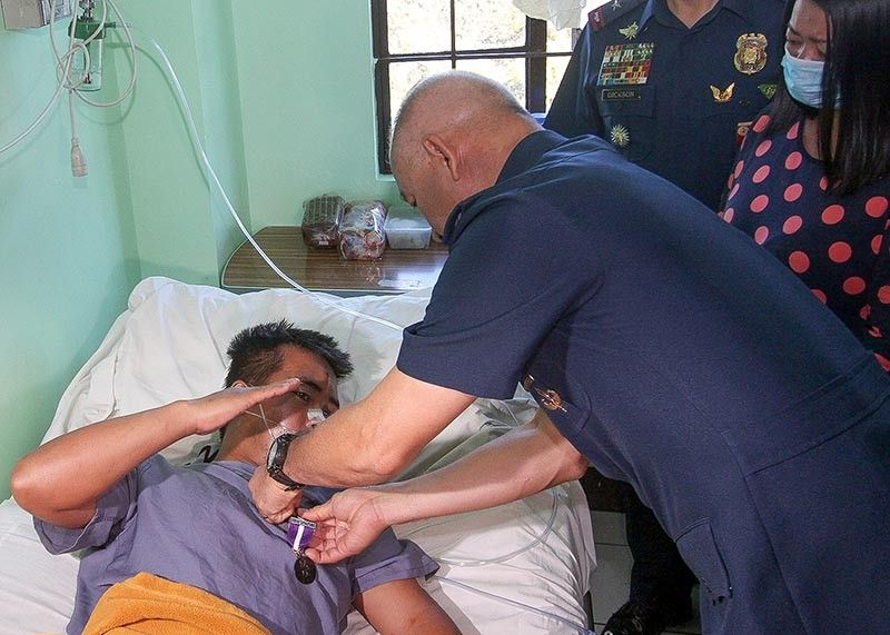 BAGUIO. Philippine National Police General Oscar Albayalde pins on Police Staff Sergeant Salvador Algalatiw on Tuesday, April 9, the Sugatang Magiting award at the Baguio General Hospital. Other police officers who were wounded during a clash with the New People's Army in Mountain Province last week also received the award. (Photo by Jean Nicole Cortes)