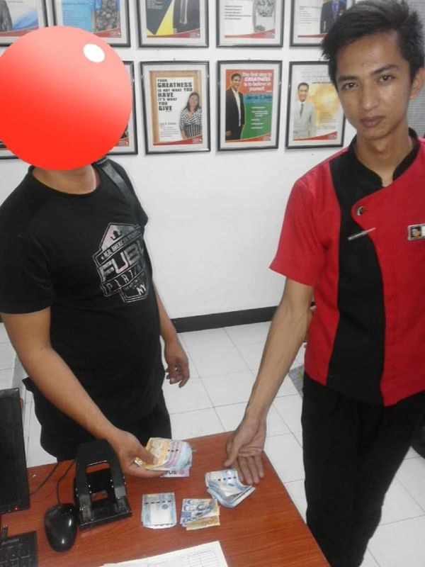 PAMPANGA. Remond Palomo, a room guide at Hotel Sogo Mexico branch, returns to the a guest the bag containing P40,515 cash and important documents on April 9, 2019. (Contributed photo)