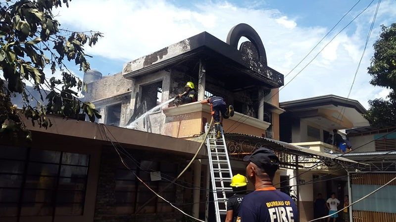 Fire fighters make it sure that Wednesday noon's blaze at the Eddie Gold compound in Barangay Carmen, Cagayan de Oro is totally under control. (Lynde Salgados)