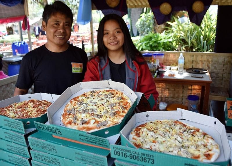 BAGUIO. Father and daughter tandem Cesar and Aiyana Agbayani from Pudtol, Apayao display the native delicacies of Apayao such as the pinalatan, binanayan and pinaltit through their homemade pizza featured in the Mangan Taku Cordillera Food Fair at the Rose Garden, Burnham Park in Baguio City from April 8 to 14. (Photo by Redjie Melvic Cawis)