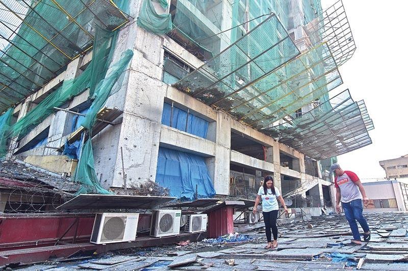 DAVAO. Gisusi sa mga maintenance personnel sa usa ka establisemento sa may dalang C.M Recto, Davao City ang atop human sige kini og katagakan og mga tipak sa semento ug usahay bakal nga nakadamyos ug nakabuslot sa atop ug power supply sa gambalay nga nakapurwesyo sa operasyon sa mga tenants sulod sa gambalay gikan sa usa ka high-rise condominium sa ilang tapad. (Macky Lim)