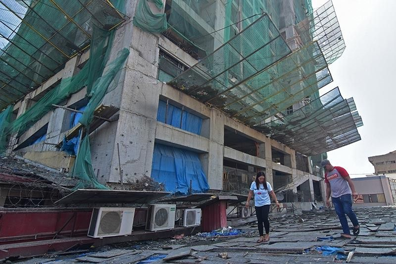 DAVAO. Maintenance personnel of a Boy Scouts of the Philippines building on CM Recto Street, Davao City inspect their roof after debris from a high-rise building next to the establishment damaged their roof and power transformer, which caused power outages and leaks inside the commercial building. (Photo by Macky Lim)