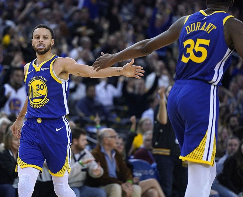 Golden State Warriors' Kevin Durant (35) high-fives Stephen Curry (30) after Curry made a 3-point shot against the Cleveland Cavaliers during the second half of an NBA basketball game Friday, April 5, 2019, in Oakland, Calif. The Warriors won 120-114. <b>(AP Photo)</b>