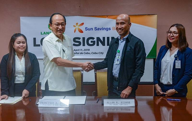 DONE DEAL. Sun Savings Bank president and chief executive officer Francisco Dizon (second from left) seals the deal with Land Bank of the Philippines Cebu South Lending Center head Allan Bisnar. The loan signing was witnessed by Sun Savings assistant vice president Marilou Saberon (left) and Landbank account assistant Krizza Paras. (SunStar Photo/Arni Aclao)