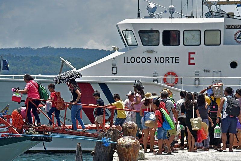"""DAVAO. Nagtapok ang mga pasahero nga pasakay, padulong og Talicud, Island Garden City of Samal (Igacos) Sabado, Abril 13 atol sa pag-abot sa bangka sa Sta. Ana Pier, Davao City. Kapin 60 ka mga bangka ang gi-monitor sa Philippine Coast Guard (PCG-Davao) sa gipagula nga """"No travel, No permit"""" policy sa lokal nga kagamhanan sa Davao City niadtong Biyernes. (Macky Lim)"""