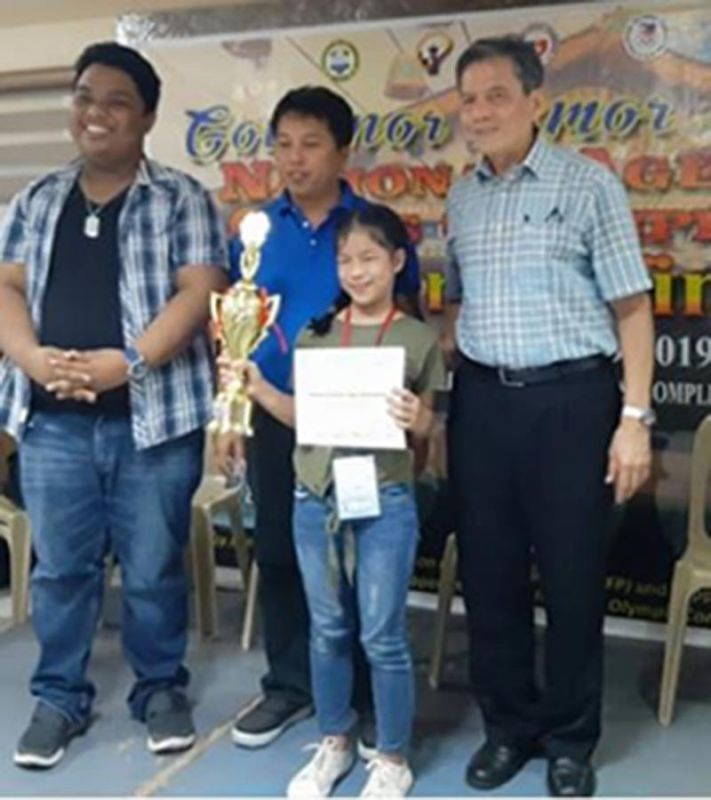 SUPER TAWING. Ruelle Canino of Cagayan de Oro receives the Girls 12-Under championship trophy from Asia's first Grandmaster Eugene Torre, at right, during the 2019 National Age Group Chess Grandfinals awards rites in Zambales. (Supplied Photo)