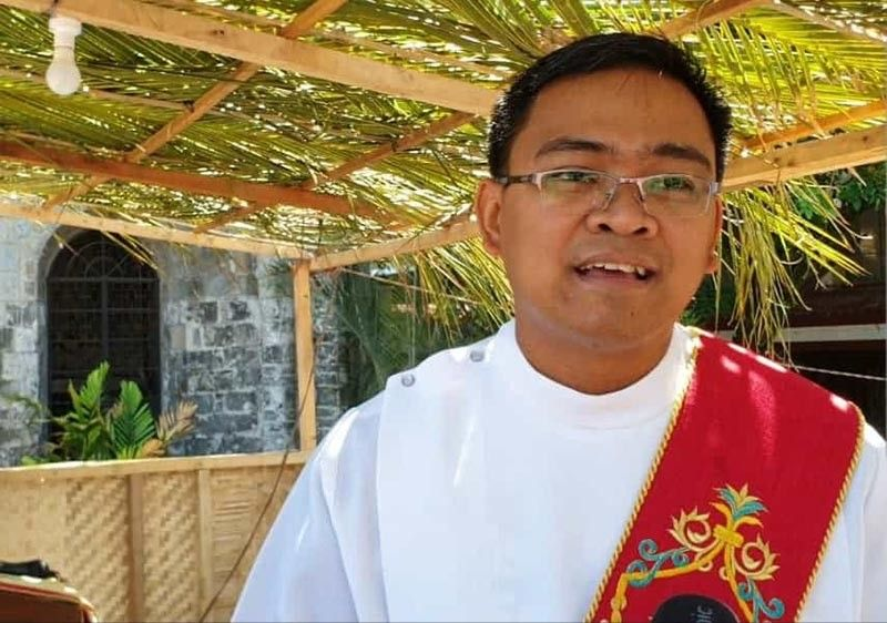 Rev. Jomar Solano, a Deacon at the Diocese of Bacolod, San Sebastian Cathedral. He blessed with holy water Palm crosses held by devout Catholics after the mass.