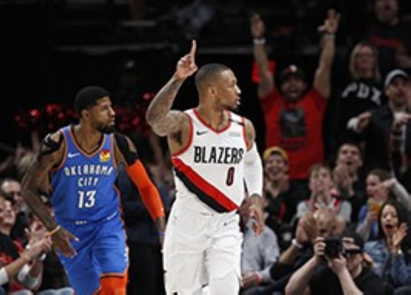 Portland Trail Blazers guard Damian Lillard, right, reacts after making a basket as Oklahoma City Thunder forward Paul George, left, trails the play during the first half of Game 1 of a first-round NBA basketball playoff series in Portland, Ore., Sunday, April 14, 2019. <B>(AP)</B>