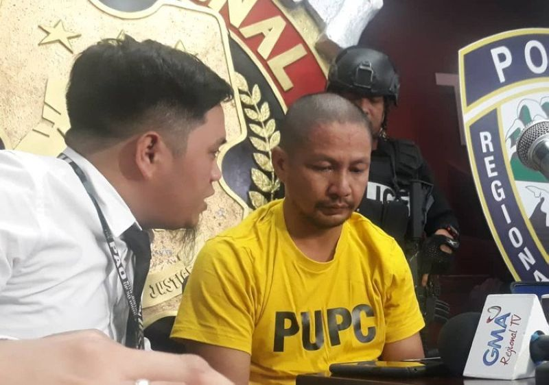 CEBU. Jessie Medequillo (wearing yellow) talks to his lawyer as he faces media following his surrender to authorities last Friday, April 8. (Alan Tangcawan)