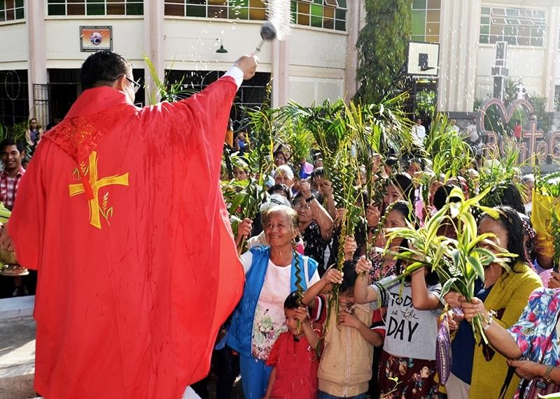 BONTOC. Father Ronilo Pagao bless parishioners of the Santa Rita de Cascia Cathedral in Poblacion, Bontoc, Mountain Province during Palm Sunday, which marks Jesus' triumphant entry into Jerusalem and the start of Holy Week. (Photo by Ferdie Cariño Castañeda)