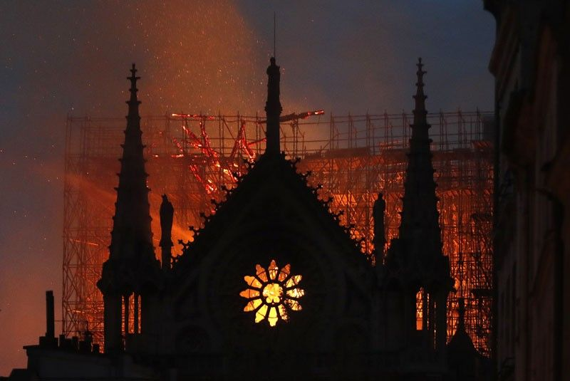 PARIS. Flames and smoke rise from Notre Dame cathedral as it burns in Paris, Monday, April 15, 2019. Massive plumes of yellow brown smoke is filling the air above Notre Dame Cathedral and ash is falling on tourists and others around the island that marks the center of Paris. (AP)
