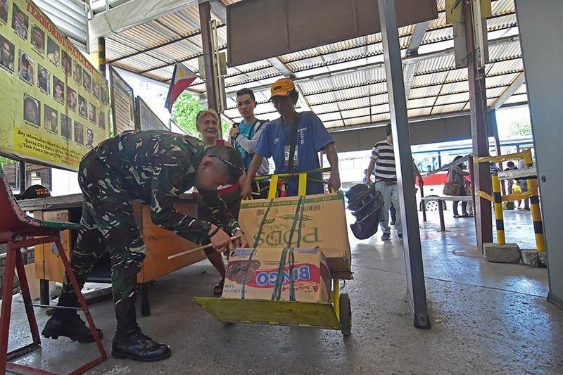 DAVAO. Gibangagan sa personahe sa Task Force Davao ang karton nga bitbit sa porter sa inspeksiyon nga gihimo sa bagahe pasulod sa Davao City Overland Transport Terminal kung diin hugot nga seguridad ang gipatuman sa mga pasahero atol sa Semana Santa. (Macky Lim)