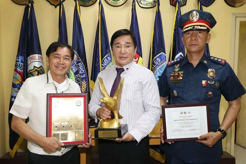 PAMPANGA. Central Luzon Regional Advisory Council officers Reghis  M. Romero II, chairman of R-II Builders Inc., former Salapungan, Angeles City Barangay Chairman Rey Malig, and Police Colonel Joyce Patrick Sangalang, commander of the Regional Mobile Force Battalion 3, receive the Golden Eagle Award on Monday, April 15, for the implementation of the PNP Patrol Plan 2030 awarding at Police Regional Office 3 in Camp Olivas, City of San Fernando, Pampanga. (Photo by Chris Navarro)