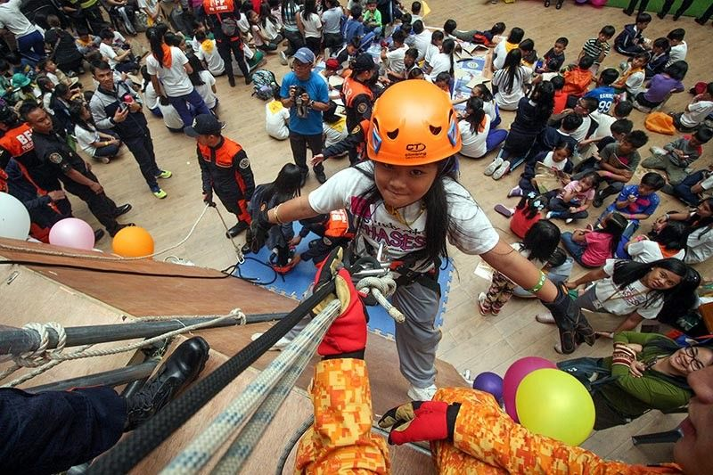 BAGUIO. More than a hundred children 7 to 12 years old experience rappelling, one of the many activities and lessons during a recent Fire Safety Roadshow in Baguio City. (Photo by Jean Nicole Cortes)