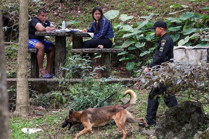 BAGUIO. A K9 and policeman roam around Burnham Park to ensure safety and security of locals and tourists visiting the area during the Holy Week. (Photo by Jean Nicole Cortes)