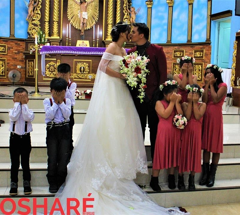 Kids cover their eyes as the newlywed kiss. (Photo by Osharé)