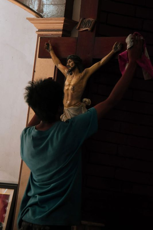 DAVAO. A church volunteer wiping Jesus' crucifix while Roman Catholic devotees are having their Visita Iglesias inside St. Jude Thaddeus Parish Church in Malvar Street, Davao City. (Ralph Lawrence Llemit)
