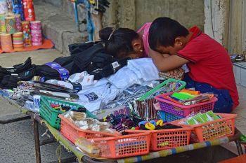 DAVAO. Tungod walay mga tawo nga nangagi sa sidewalk, nag-iyahay og tulog kining duha ka mga bata nga nagbantay sa ilang mga baligya kilid sa San Pedro Extension, Davao City, Sabado, Abril 20, 2019. (Macky Lim)