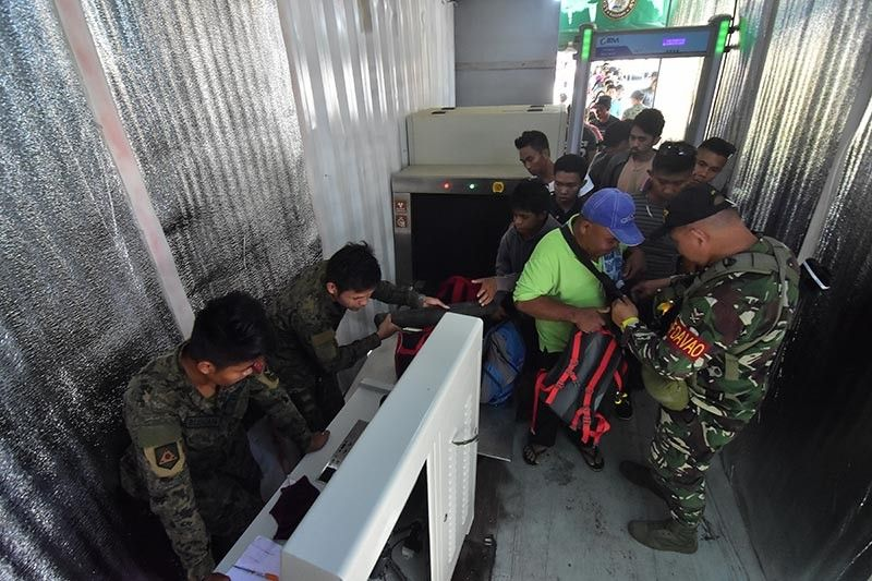 DAVAO. Task Force Davao personnel man the newly installed x-ray machines for public utility vehicle passengers upon entering Davao City at the checkpoint in Toril, Davao City to ensure tighter security check. (Macky Lim)
