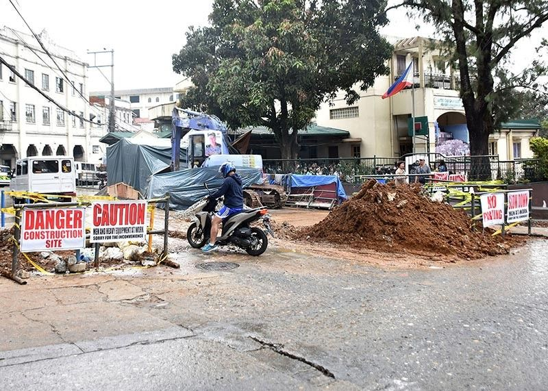 BAGUIO. Motorists and pedestrians endure the mud and water from the construction area along the Rizal Park to rehabilitate the gutters and drainage. (Photo by Redjie Melvic Cawis)