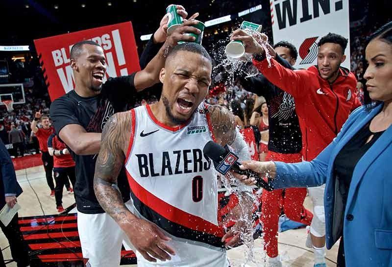 ANG BAYANI. Si Damian Lillard (0) sa Portland Trail Blazers nga gibuboan og tubig sa iyang mga kauban samtang gi-interview kini tugnod sa iyang bayanihong itsa sa three-point area nga maoy nagtigbak sa paglaom sa Oklahoma City Thunder sa Game 4 sa ilang first round sa playoff series kagahapon. Ang Portland midaog, 118-115, aron paglabni og luna sa Western Conference semis. (AP)