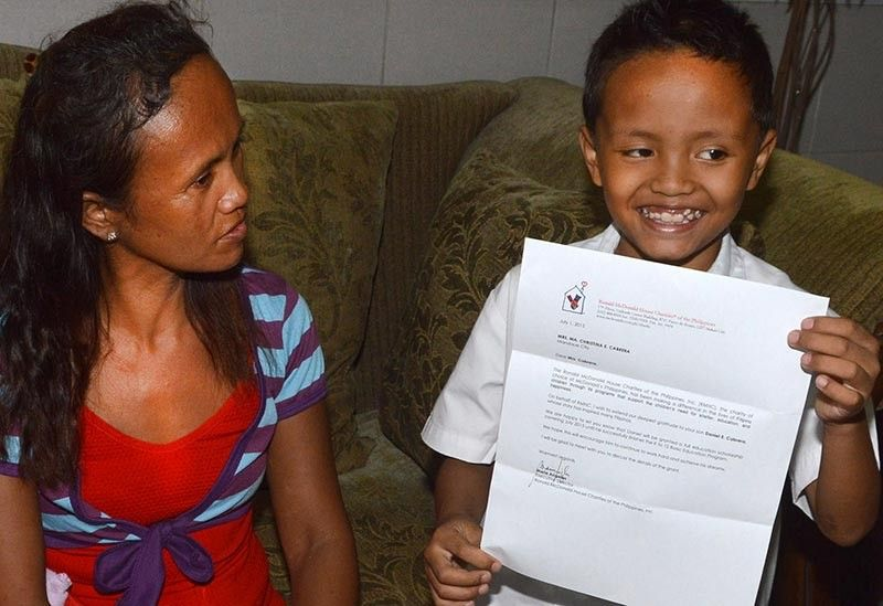 "INSPIRING. Daniel ""Biboy""  Cabrera, then 9, showing his scholarship grant from Ronald McDonalds House of Charities Philippines. (SunStar file)"