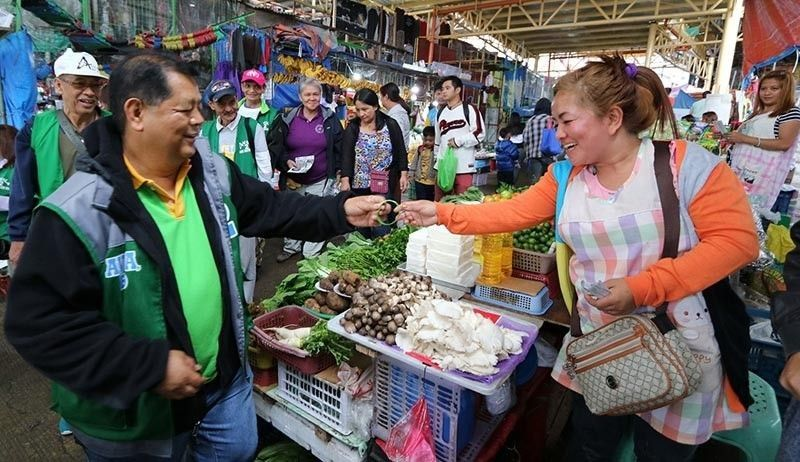 BAGUIO. Baguio City mayoral bet Edgar Avila distributes wristbands during his sortie at the Baguio City Public Market. (Contributed photo)