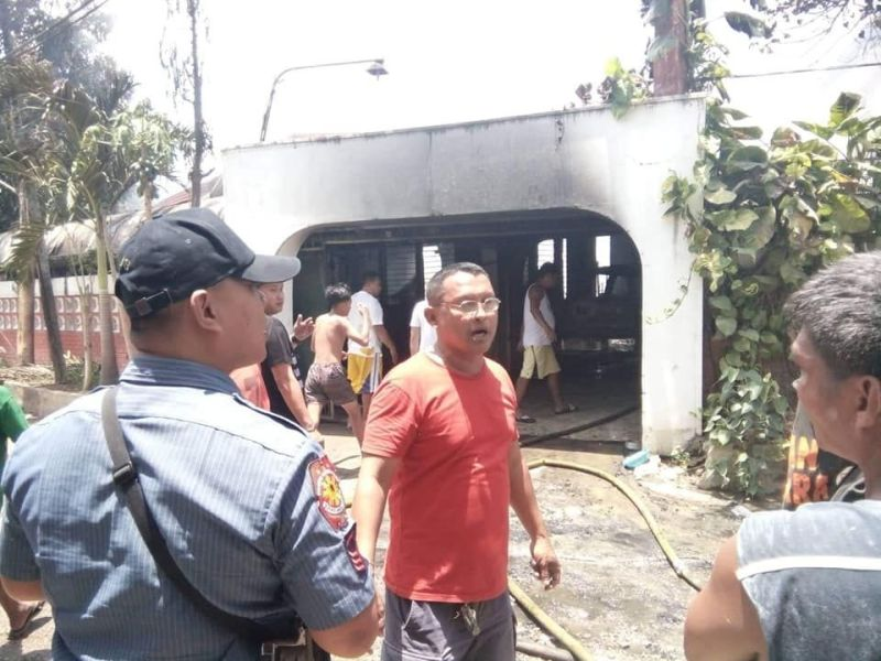 CEBU. Local police officers survey the remnants of the house of Engr. Nazario Parsacala in Belmont Village, Minglanilla town after it was hit by fire on Friday, April 26. Though Parsacala and his wife Virginia only sustained burns, their seven-year-old grandson, Justin, died after he was trap inside his room. (Contributed photo courtesy of Police Master Sergeant Gilmer Noval of the Minglanilla Police Station)