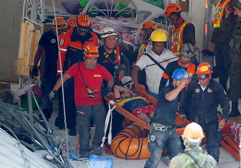 PAMPANGA. Rescuers carry an earthquake survivor after being pulled out from the rubble of a commercial building following a 6.1 magnitude earthquake in Porac, Pampanga on Tuesday, April 23, 2019. (AP)