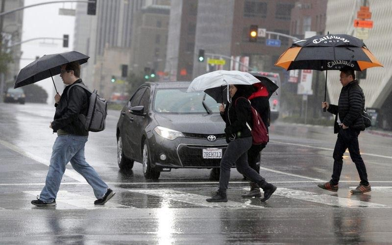 PEDESTRIANS cross a rainy street in downtown Los Angeles in February, 2017. According to a study released in April 2019 in the Bulletin of the American Meteorological Society, even light rain significantly increases the rise of a fatal car crash. (AP Photo)