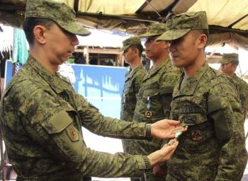 BACOLOD. Brigadier General Benedict Arevalo, commander of 303rd Infantry Brigade of the Philippine Army pins a military commendation medal to one of the personnel of the 62nd Infantry Battalion (IB) at their headquarters in Isabela, Negros Occidental Wednesday, April 24, 2019. (303rd Infantry Brigade Photo)
