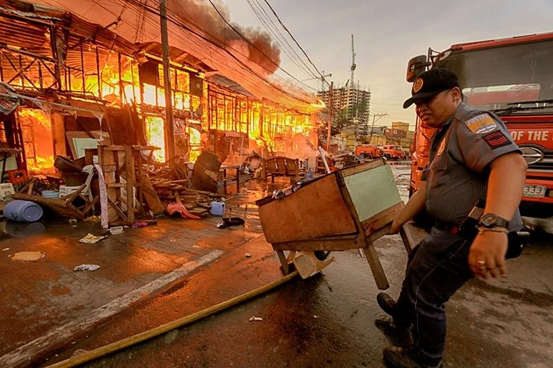 POLICE HELP. A police officer helps carry some belongings out of the way of the fire that hit Sitio Silangan 2, Barangay Tejero, Cebu City on Friday, April 26. The area is near the port. (SunStar photo / Alex Badayos)
