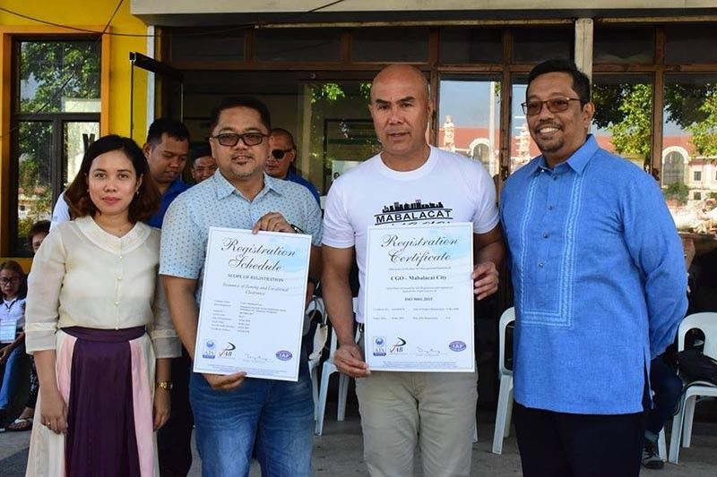Mabalacat City Mayor Cris Garbo and City Administrator chief Rosan Paquia receive from AJA Registrars president Paul Bagatsing and Business Development and Client Relations manager Laarni Narido the ISO 9001:2015 certification the City Planning and Development Office earned for instituting standards on zoning and location clearance. (SunStar Pampanga)