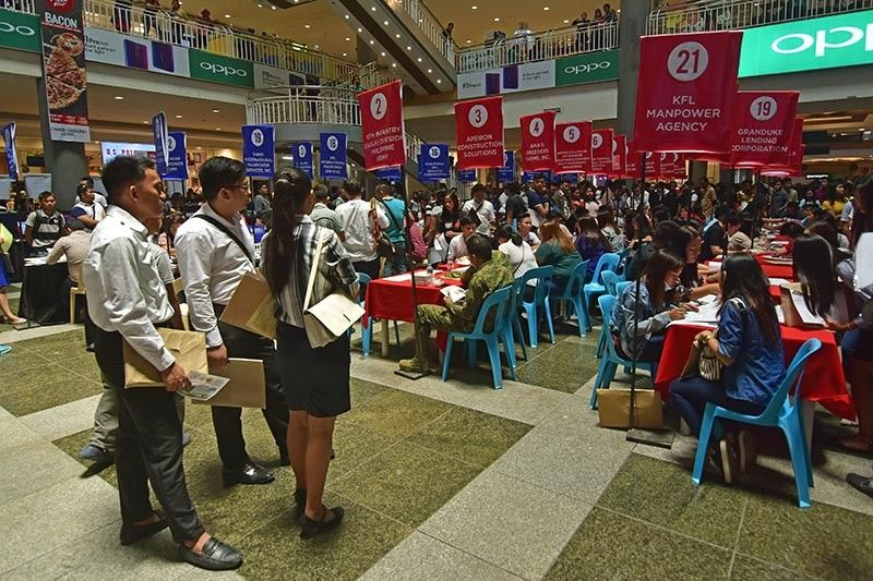 DAVAO. A group of fresh graduates stand at the side as they scout for employers during Wednesday's (May 1) Labor Day Jobs Fair at a mall in Davao City, where almost 8,000 jobs, local and overseas, are up for grabs. (Macky Lim)