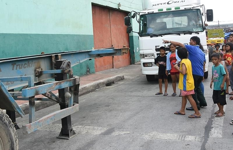 SITE OF TRAGEDY. Onlookers check the area where three girls got run over by a trailer truck in Sitio Silangan, Barangay Tejero, Cebu City. (SunStar photo / Allan Cuizon)